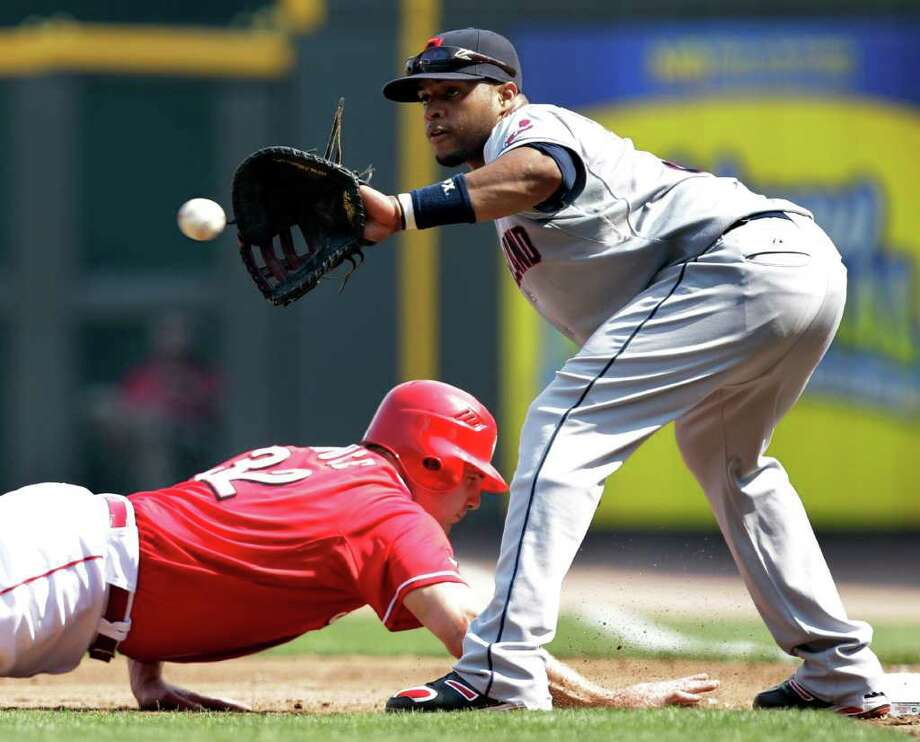Cincinnati Reds' Jay Bruce (32) dives safely back to first as Cleveland Indians first baseman Carlos Santana catches the pickoff-attempt in the second inning of an interleague baseball game on Saturday, July 2, 2011, in Cincinnati. (AP Photo/Al Behrman) Photo: Al Behrman, STF / AP