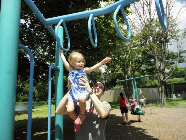 Leah Larit, 2, of Westport, swings on the monkey bars with help from her father, Keith, on Saturday at the playground in Longshore Club Park. Photo: Meg Barone / Westport News freelance