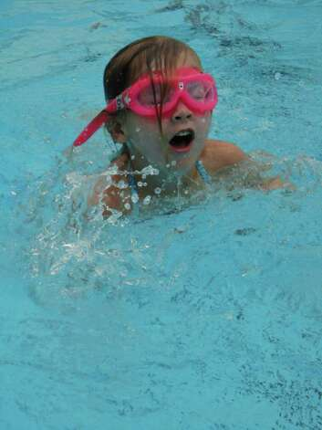 Alexandra Lieber, 4, of Westport, sporting pink goggles, comes up for air after swimming underwater in the Longshore pool Saturday. Photo: Meg Barone / Westport News freelance