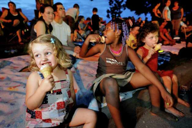 Holly VanValkenburgh, 2, of Niskayuna, left, eats ice cream as she waits for the fireworks show to start on Friday, July 1, 2011, at Freedom Park in Scotia, N.Y. Joining Holly are her friend Ashley Hall, 6, of Brooklyn, center, her sister Samantha, 4, and parents Nina and Paul VanValkenburgh. (Cindy Schultz / Times Union) Photo: Cindy Schultz