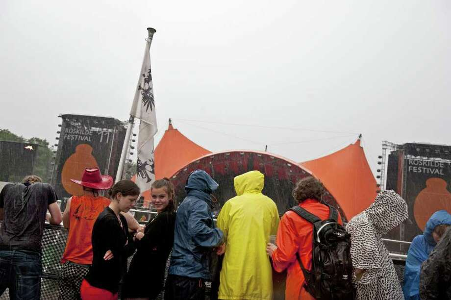 Music fans stand in heavy rainfall at the Roskilde Festival 2011 on Saturday, July 2, 2011. 75,000 people gathered for the festival that lasts until Sunday.  (AP Photo/POLFOTO, Helle Arensbak)  DENMARK OUT Photo: Helle Arensbak
