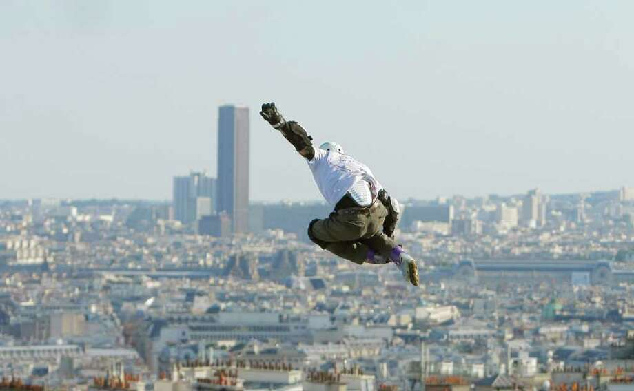 French roller skate champion Taig Kriss as he sails through the air from the large platform, to jump 150 meters (500 feet) in front of the Paris skyline Saturday, July 2, 2011.  The extreme inline roller blade jump was done just for fun. Tall building behind, Montparnasse Tower.(AP Photo/Jacques brinon) Photo: Jacques Brinon / AP