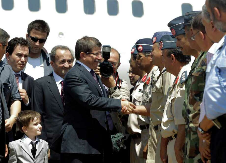 Turkish foreign minister Ahmet Davutoglu, center, with his son, bottom left, shakes hands with officials from the rebel stronghold of Benghazi, Libya, upon his arrival Sunday, July 3, 2011. (AP Photo/Sergey Ponomarev) Photo: Sergey Ponomarev / AP