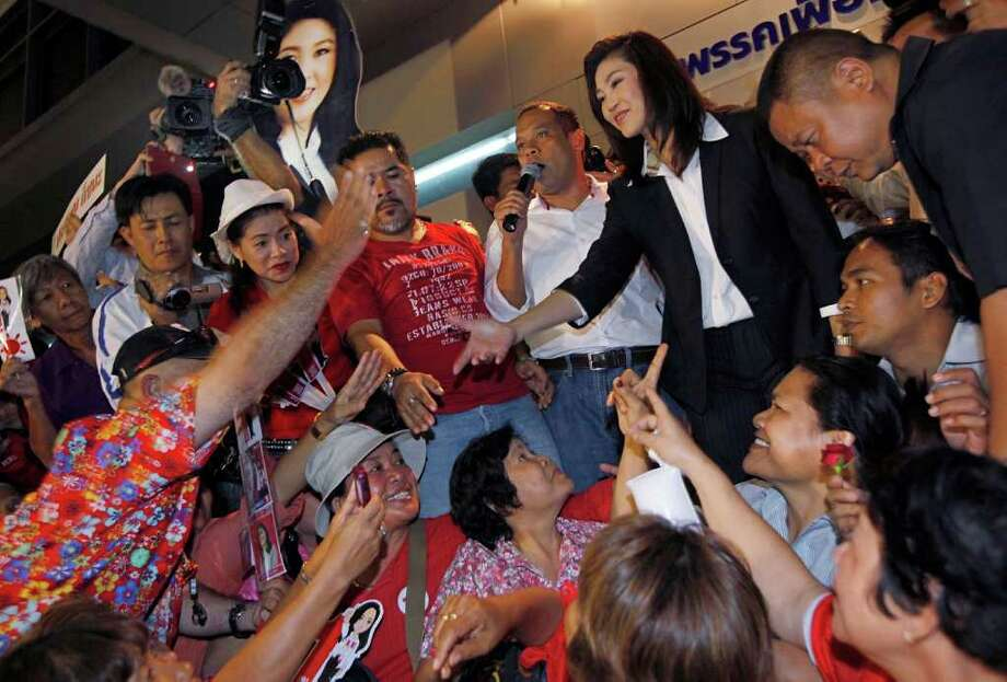 Yingluck Shinawatra, opposition Pheu Thai Party's candidate for prime minister shakes hands with supporters as she celebrates after winning the election at the party headquarters in Bangkok on Sunday, July 3, 2011.  The sister of exiled former Prime Minister Thaksin Shinawatra, Yingluck led Thailand's main opposition party to a landslide victory in elections Sunday, heralding an extraordinary political turnaround five tumultuous years after her fugitive billionaire brother was toppled in an army coup, and paving the way Yingluck Shinawatra, who has never held office, to become this Southeast Asian kingdom's first female prime minister. (AP Photo/Vincent Yu) Photo: Vincent Yu / AP