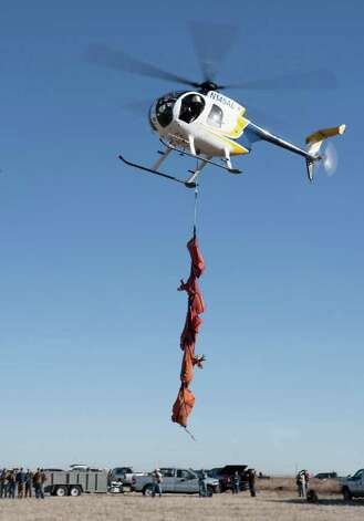 Biologists with Texas Parks & Wildlife begin the helicopter trapping of 200 pronghorn in the Dalhart area on February 23, 2011. Using net guns, crew members ensnare a pronghorn from above, then jump from the low-hovering helicopter to quickly blindfold and hobble the animal. Snug in a sling, it and up to four companions are flown to a staging area for examination and aging by veterinarians and biologists. The pronghorn were relocated to Marfa to help repopulate the Big Bend area. Photo: Courtey Photo/Texas Parks & Wildlife / Texas Parks & Wildlife Department