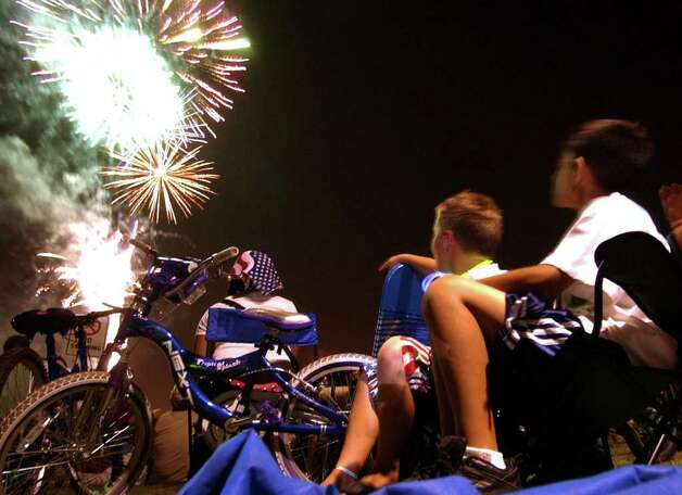 Jeffrey Jordan (left) and Brandon Haynes watch fireworks light up the night over Woodlawn Lake during the Independence Day celebration on Sunday, July 4, 2004. Photo: Billy Calzada/gcalzada@express-news.net