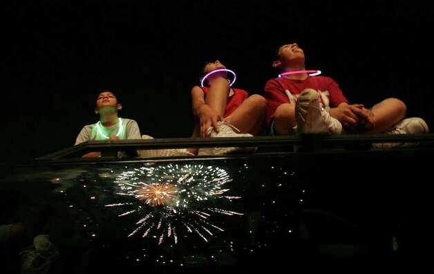 Henry Guzman, 11, Jessica Guzman, 12, and Frank Guzman, 11, watch the fireworks during Hope Events' Freedom Reigns, an Independence Day celebration hosted by First Assembly of God on Monday, July 4, 2005. Photo: Lisa Krantz/lkrantz@express-news.net / SAN ANTONIO EXPRESS-NEWS