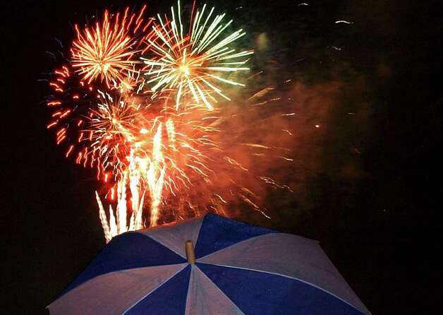 A spectator watches the fireworks display at Woodlawn Lake on Tuesday, July 4, 2006, from under the cover of an umbrella as rainy skies put a damper on the celebration. Photo: Tom Reel/treel@express-news.net / SAN ANTONIO EXPRESS-NEWS