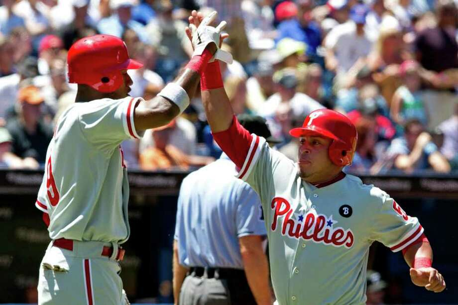 Philadelphia Phillies' Carlos Ruiz, right, and teammate Domonic Brown celebrate after scoring on a single by Jimmy Rollins during the second inning of a baseball game, Sunday, July 3, 2011, in Toronto. (AP Photo/The Canadian Press, Darren Calabrese) Photo: Darren Calabrese