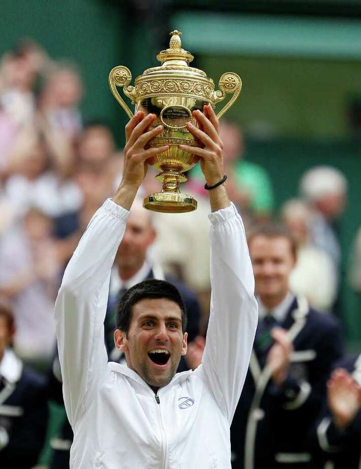 Serbia's Novak Djokovic lifts the trophy after defeating Spain's Rafael Nadal in the men's singles final at the All England Lawn Tennis Championships at Wimbledon, Sunday, July 3, 2011. (AP Photo/Alastair Grant) Photo: Alastair Grant
