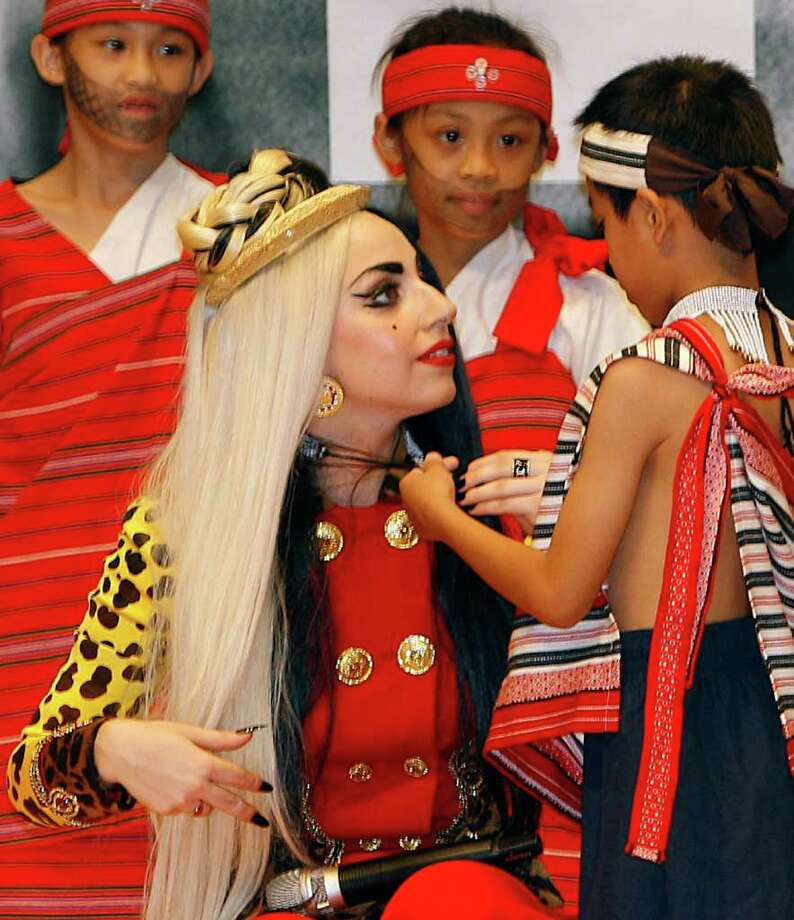 "International pop diva Lady Gaga receives a necklace from a group of performing indigenous Taiwanese children at a welcoming ceremony during a ""Lady Gaga Day"" in Taichung, Taiwan, Sunday, July 3, 2011. Photo: AP"