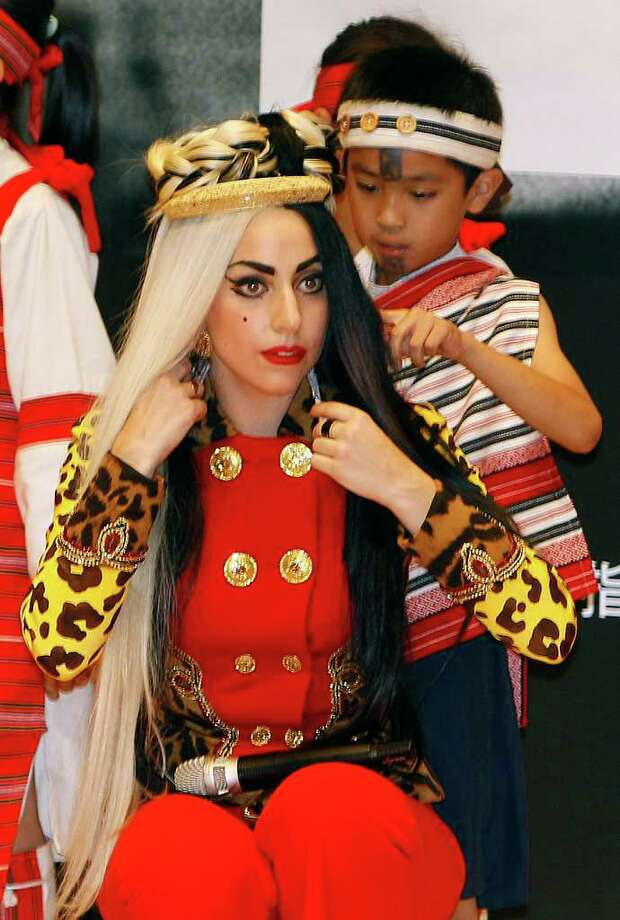 "International pop diva Lady Gaga receives a necklace from a group of performing indigenous Taiwanese children during a welcoming ceremony on ""Lady Gaga Day"" in Taichung, Taiwan, Sunday, July 3, 2011. Lady Gaga is visiting Taiwan for five days promoting her new album ""Born This Way."" Photo: AP"