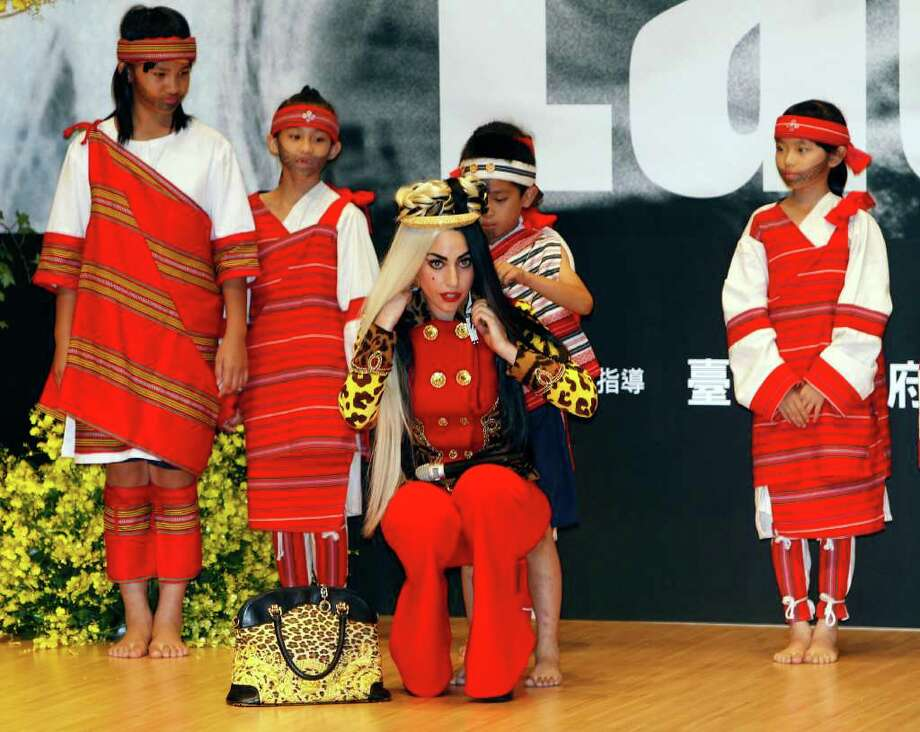 International pop diva Lady Gaga receives a necklace from a group of performing indigenous Taiwanese children during a welcoming ceremony in Taichung, Taiwan, Sunday, July 3, 2011. Photo: AP