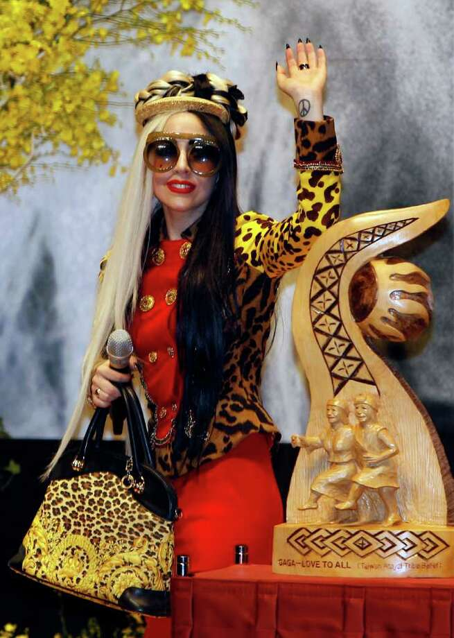 International pop diva Lady Gaga waves from behind a wood carving gift during a welcoming ceremony in Taichung, Taiwan, Sunday, July 3, 2011. Photo: AP