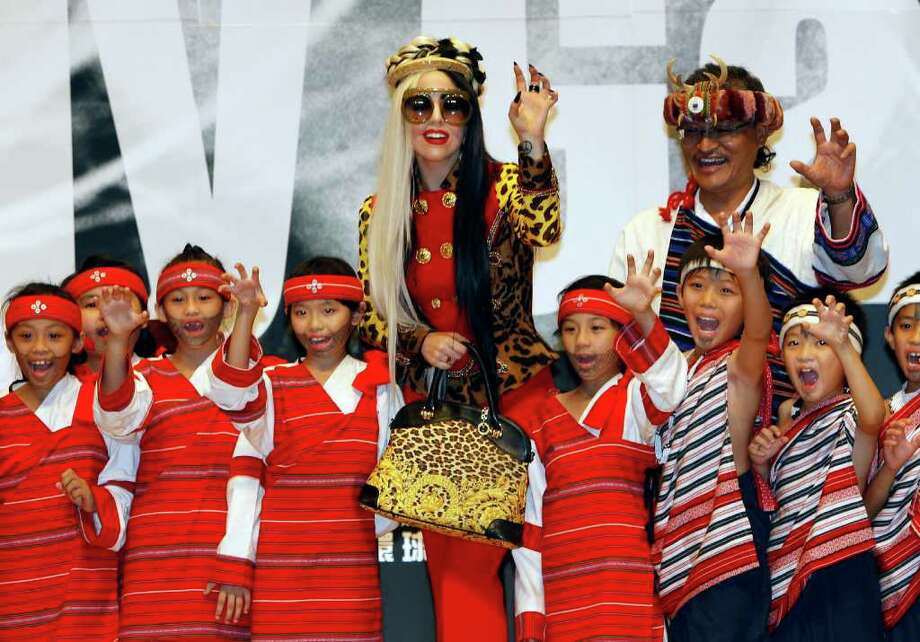 "International pop diva Lady Gaga gives signature paw sign with a group of performing indigenous Taiwanese children during a welcoming ceremony during a ""Lady Gaga Day"" in Taichung, Taiwan, Sunday, July 3, 2011. Photo: AP"