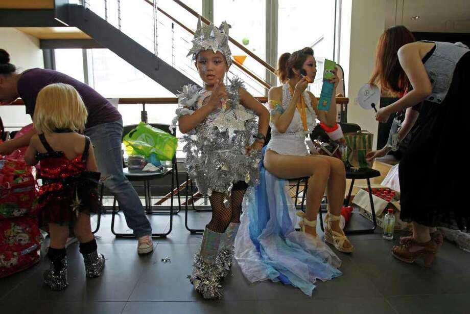 "A young fan of international pop sensation Lady Gaga strikes a pose as fans prepare their costumes during a ""Lady Gaga Day"" fashion show before her evening mini concert in Taichung, Taiwan, Sunday, July 3, 2011. Photo: AP"