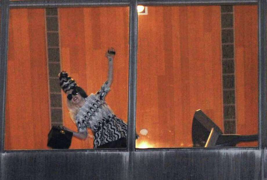 "International pop diva Lady Gaga waves to fans from a hotel window after arriving in Taipei, Taiwan, July 1, 2011. Lady Gaga slipped into the hotel unbeknownst to the waiting crowd of fans. Lady Gaga is in Taiwan for five days on a promotional tour for her new album ""Born This Way."" Photo: AP"