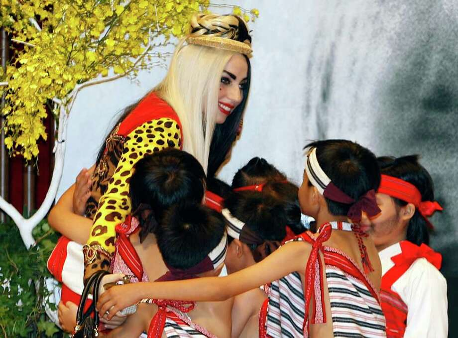 "International pop diva Lady Gaga shares a hug with a group of performing indigenous Taiwanese children during a welcoming ceremony on a ""Lady Gaga Day"" in Taichung, Taiwan, Sunday, July 3, 2011. Photo: AP"