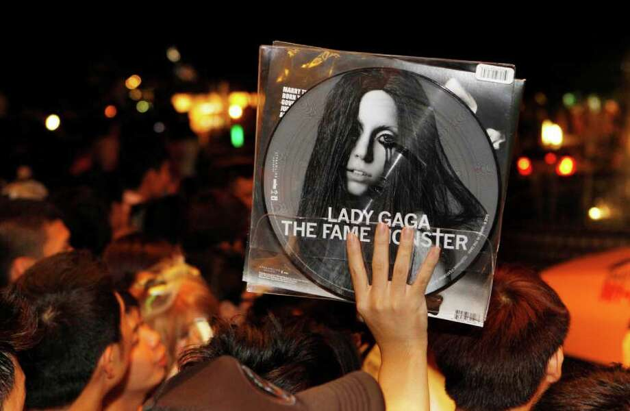 "A fan holds up an album as they wait for international pop diva Lady Gaga to arrive at her hotel in Taipei, Taiwan, Friday, July 1, 2011. Lady Gaga slipped into the hotel unbeknownst to the waiting crowd of fans. Gaga is in Taiwan for five days on a promotional tour for her new album ""Born This Way."" Photo: AP"