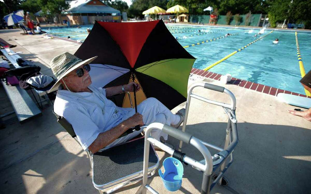 Bud Dallmann sits poolside at Landa Park, using an umbrella for shade. He had a 42-year military career in the Air Force.