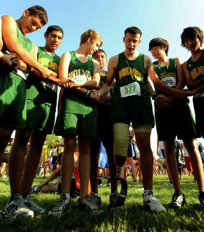Matthew Patino (377) leads his cross country teammates in prayer before a race at Mission County Park on Sept. 15, 2010. Patino lost his right leg to cancer. Photo: Billy Calzada/gcalzada@express-news.net / gcalzada@express-news.net
