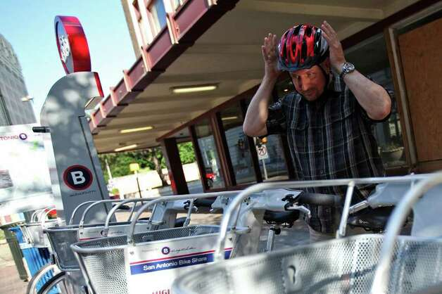 Philip Schrank, owner of Gallery Vetro, prepares to ride a B-Cycle bike home at the East Houston Street stand on June 23, 2011. Schrank is the B-Cycle bike-sharing system's top users with around 750 miles. Photo: Andrew Buckley/abuckley@express-news.net / abuckley@express-news.net