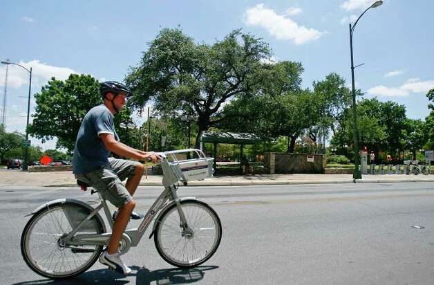 Robert Young gets some exercise on a bike from the B-cycle bike sharing system on Monday, June 27, 2011, on West Houston Street by Milam Square.  Young is one of the top riders in the system. Photo: Sally Finneran/sfinneran@express-news.net / sfinneran@express-news.net