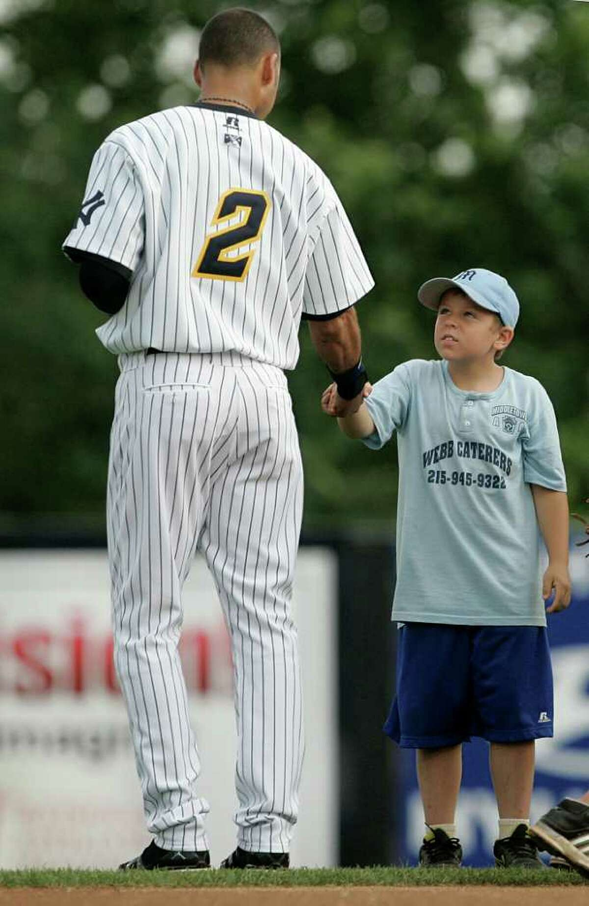 TRENTON, NJ - JULY 2: Derek Jeter of the New York Yankees shakes hands with a young boy after the national anthem during his minor league rehab start with the Trenton Thunder in a game against the Altoona Curve on July 2, 2011 at Mercer County Waterfront Park in Trenton, New Jersey. Jeter is set to rejoin the Yankees in Cleveland on Monday in his return from a calf injury. (Photo by Rich Schultz/Getty Images)