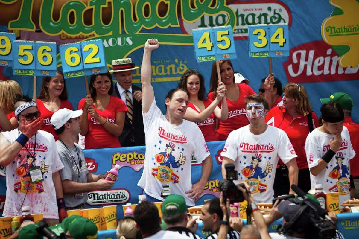 NEW YORK, NY - JULY 4: Joey Chestnut (C) celebrates winning at the end of the 2011 Nathan's Famous Fourth of July International Hot Dog Eating Contest at the original Nathan's Famous in Coney Island on July 4, 2011 in the Brooklyn borough of New York City. Chestnut also known as 'Jaws' won this year's competition by eating 62 hot dogs. (Photo by Ramin Talaie/Getty Images)
