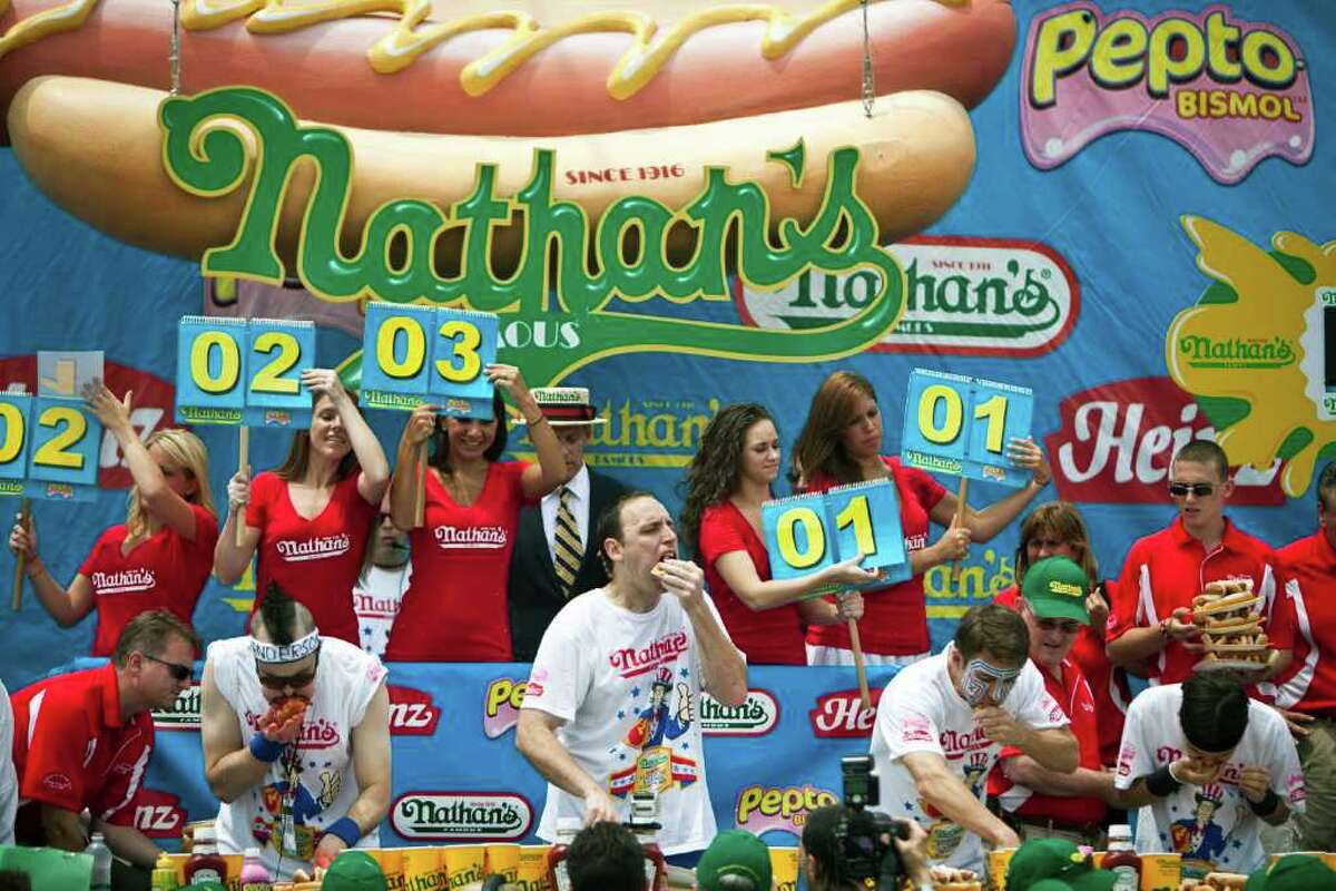 NEW YORK, NY - JULY 4: Joey Chestnut (C) competes in the 2011 Nathan's Famous Fourth of July International Hot Dog Eating Contest at the original Nathan's Famous in Coney Island on July 4, 2011 in the Brooklyn borough of New York City. Chestnut also known as 'Jaws' won this year's competition by eating 62 hot dogs. (Photo by Ramin Talaie/Getty Images)
