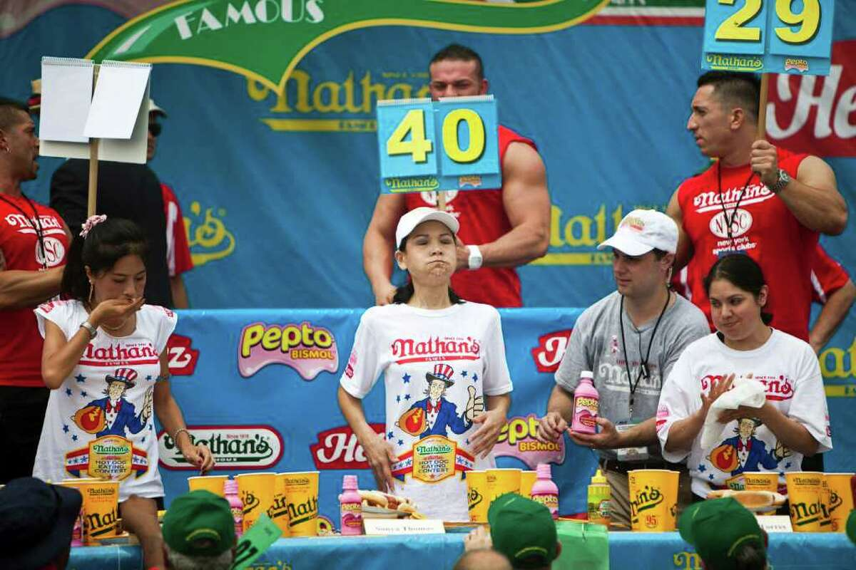NEW YORK, NY - JULY 4: Sonya Thomas (C) competes in the 2011 Nathan's Famous Fourth of July International Hot Dog Eating Contest at the original Nathan's Famous in Coney Island on July 4, 2011 in the Brooklyn borough of New York City. Thomas also known as 'The Black Widow' won this year's first ever women's competition by eating 40 hot dogs. (Photo by Ramin Talaie/Getty Images)