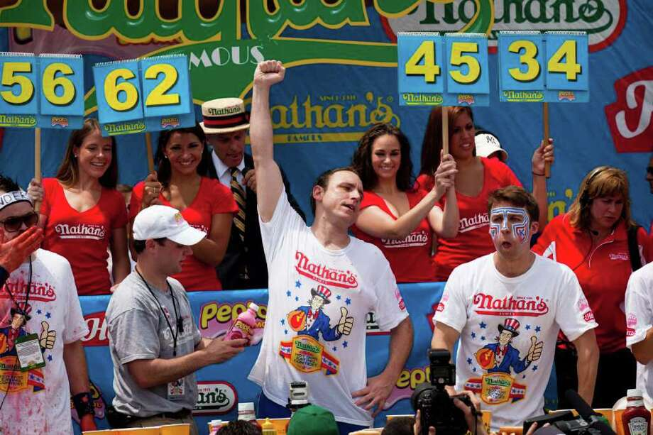 Four-time reigning champion Joey Chestnut, center, raises his arm in victory as he wins his fifth Nathan's Famous Hot Dog Eating World Championship with a total of 62 hot dogs and buns, Monday, July 4, 2011, at Coney Island, in the Brooklyn borough of New York.  (AP Photo/John Minchillo) Photo: John Minchillo