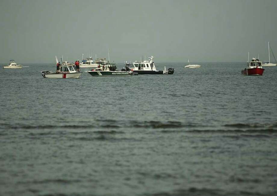 Emergency response boats recover the body of a man swept from the Charles Island sandbar, Monday afternoon, July 4, 2011 at Silver Sands State Park in Milford. Photo: Brian A. Pounds / Connecticut Post