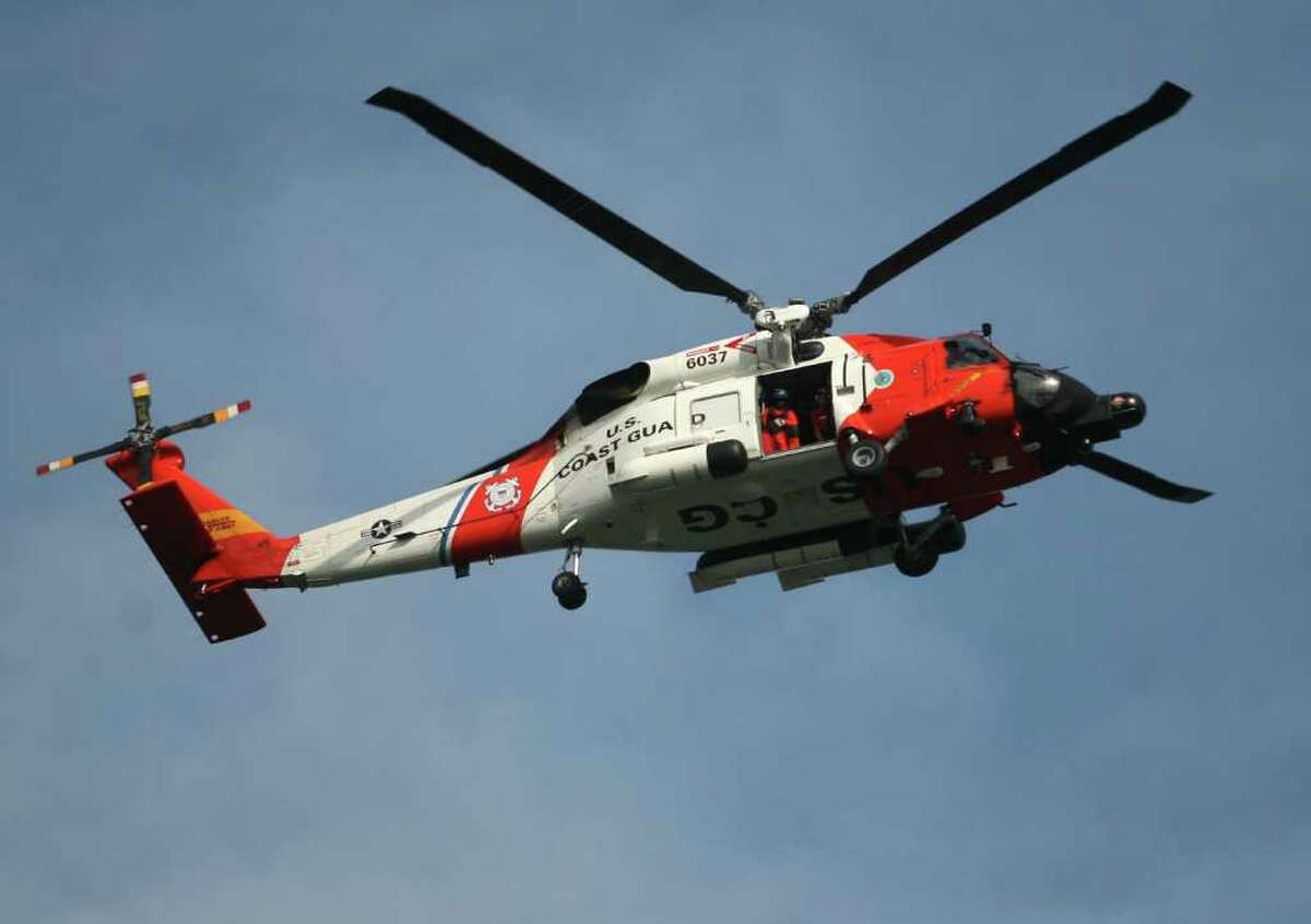 A Coast Guard rescue helicopter searches for the body of a man swept from the Charles Island sandbar, Sunday afternoon, July 4, at Silver Sands State Park in Milford.