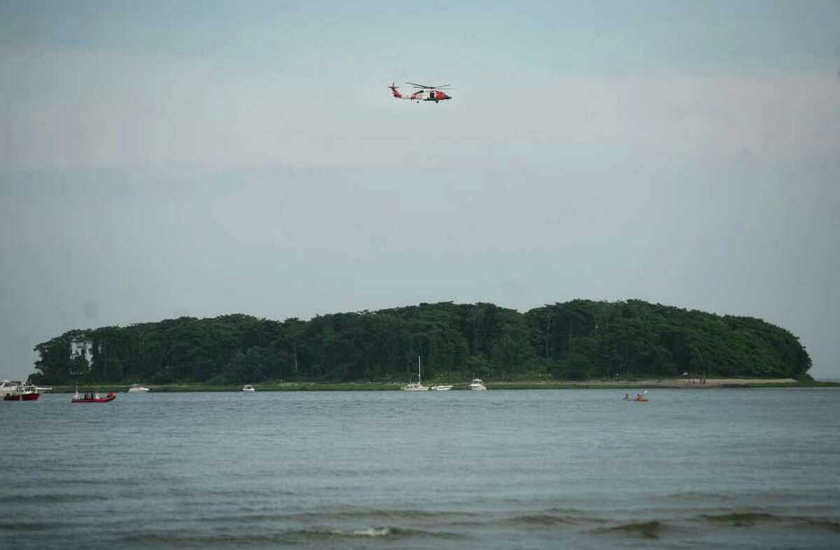 A Coast Guard rescue helicopter and rescue boats search for the body of a man swept from the Charles Island sandbar, Sunday afternoon, July 4, at Silver Sands State Park in Milford.