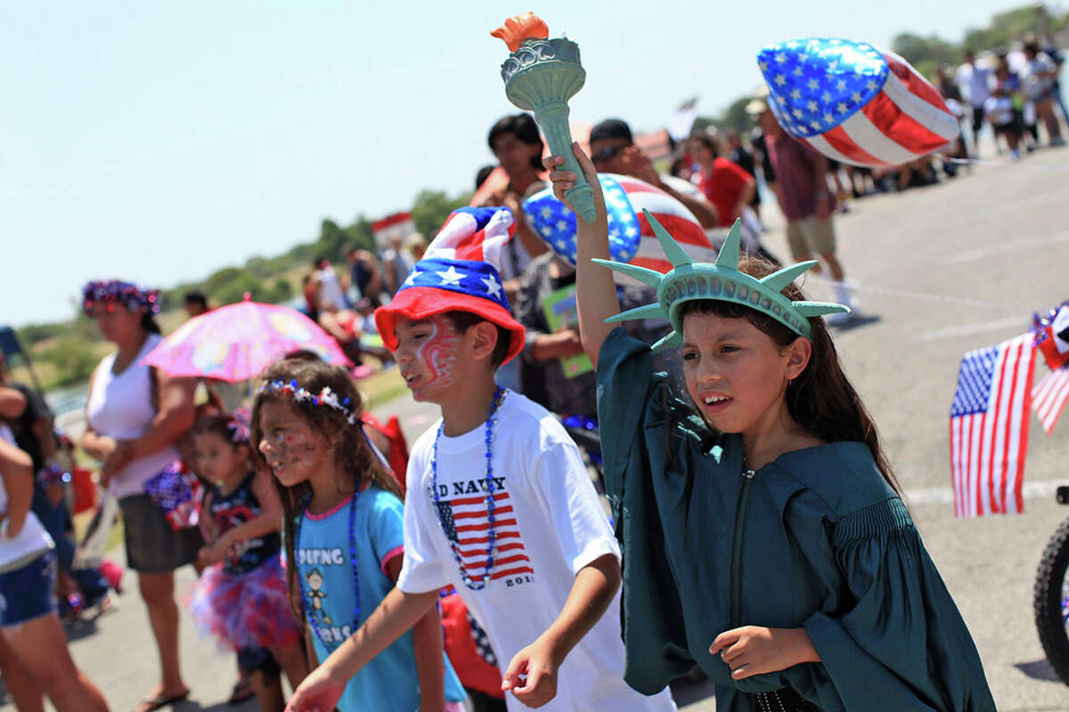 Abigail Garcia, 8,(right) with her cousin, Phillip Garcia II, 8, and her sister, Alyssa Garcia (left) cheer with parade participants after the