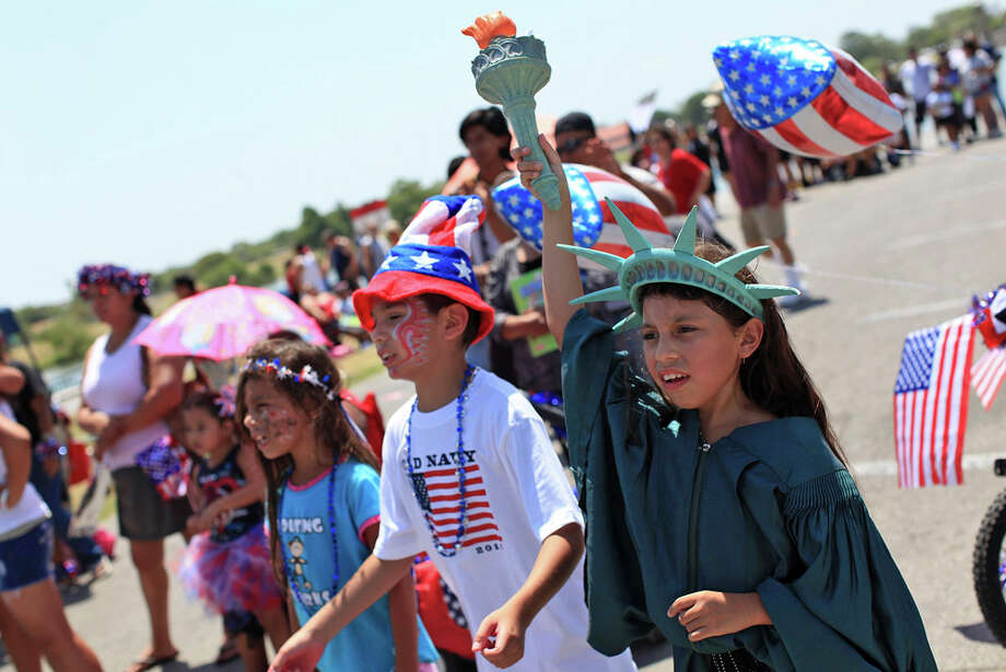 """Abigail Garcia, 8,(right) with her cousin, Phillip Garcia II, 8, and her sister, Alyssa Garcia (left) cheer with parade participants after the """"Salute to the Red, White and Blue Parade"""" at Woodlawn Lake Park in San Antonio on July 4, 2011. Photo: LISA KRANTZ / lkrantz@express-news.net"""