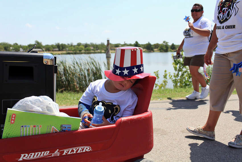 Vini Acosta-Torres, 3, sleeps in a wagon also holding the speaker for the music for the BearsNation cheerleaders during the