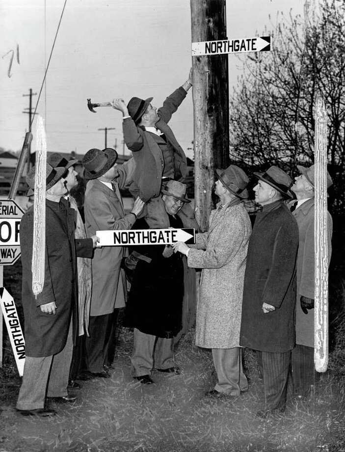The March 1950 photo caption read: North End business men are shown installing new signs throughout the district which point the way to the new Northgate shopping center. Tracy Owen, president of the North City Community Club, rears back and drives a nail, aided by Louis W. Messer, president of the Pinehurst Community Club. He is steadied by Ross E. Donald, manager of the Edmonds branch of the National Bank of Commerce. Holding another sign are Eddie G. Wassell, left, service manager of the Northgate Company, and Harold Bracken, vice president of the Associated Clubs of the North End. Others in the picture are, left to right, Dean Worthington, president of the Bothell State Bank; Dwight Hawley of Ballard Commercial Club, and Arthur W. Bell of Green Lake Commercial Club. [When this photo ran in the Post-Intelligencer, it was altered to make Bell appear closer to the others and to fit the image on the page.] Photo: Seattlepi.com File