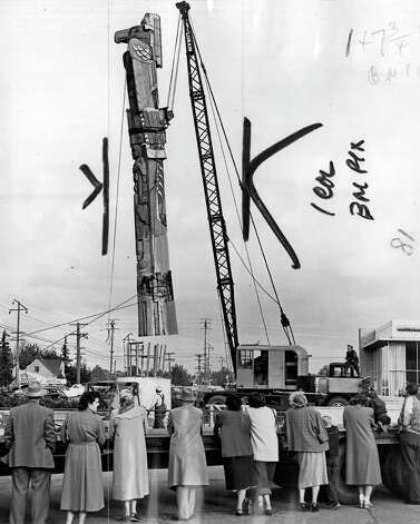 The Nov. 1952 photo caption read: Swung by a giant crane, a 54-foot totem pole carved by Dudley Carter of Bellevue was lifted into place at Northgate Saturday. Pole was corseted with wooden splints to prevent damage from cables. [Marks were made by a P-I photo editor] Photo: Seattlepi.com File