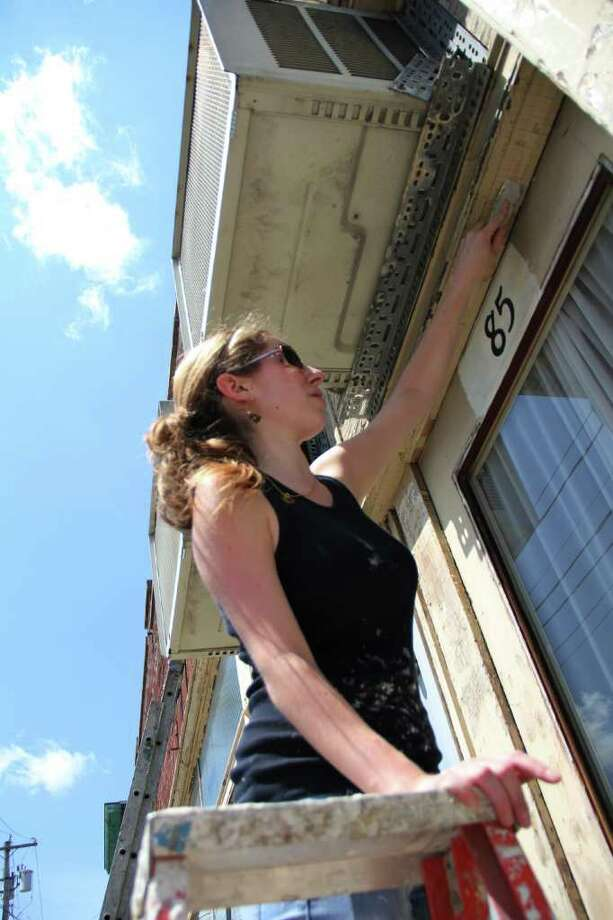 Genny Faist, Memberships Program coordinator at the Historic Albany Foundation, scrapes paint from the exterior of the Albany building on Thursday, June 30, 2011 to prepare it for a fresh coat of paint. (Erin Colligan / Special To The Times Union) / 00013715A