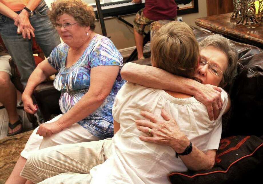 Barbara Jean Hill of Tulsa, Okla., hugs a newly found family member while reuniting with her long-lost sister, Sarah Jane Scales, left, of Orangefield. The sisters were reunited on Friday for the first time since Hill was put up for adoption in 1932. Tammy McKinley/The Enterprise