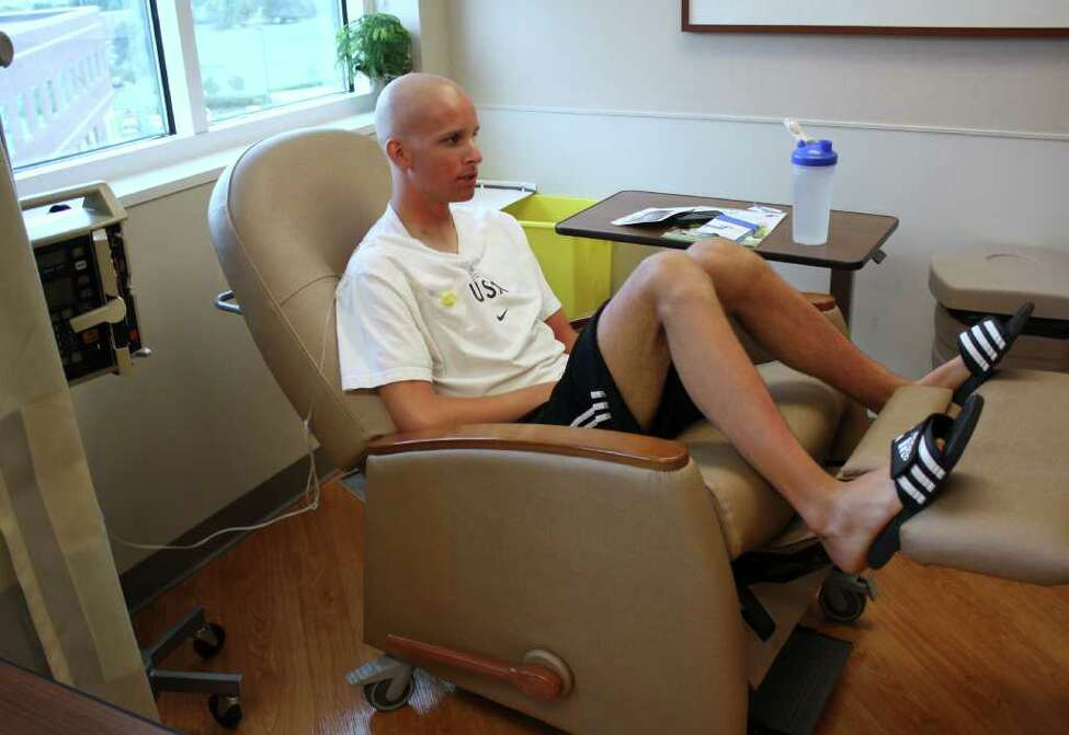 In this photo taken June 27, 2011, Kevin McDowell sits for a chemotherapy treatment in Geneva, Ill. McDowell, an elite triathlete from suburban Chicago, was diagnosed this spring with Hodgkin's lymphoma, causing him to have to withdraw from competing this September in the Junior World Championships in China, where he was a favorite to win. His friend and teammate Lukas Verzbicas, who has committed to running at the University of Oregon, made the decision to compete in McDowell's place to honor his friend. (AP Photo/Martha Irvine)