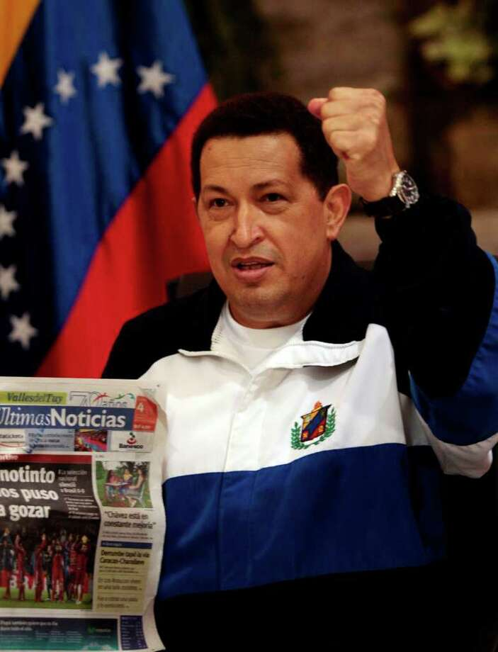 Venezuela's President Hugo Chavez raises his arm as he holds a Venezuela's newspaper in Caracas, Venezuela, Monday July 4, 2011. Chavez made a surprise return to Venezuela from Cuba before dawn Monday, saying he is feeling better as he recovers from surgery that removed a cancerous tumor. (AP Photo/Ismael Francisco, Prensa Latina) Photo: Ismael Francisco