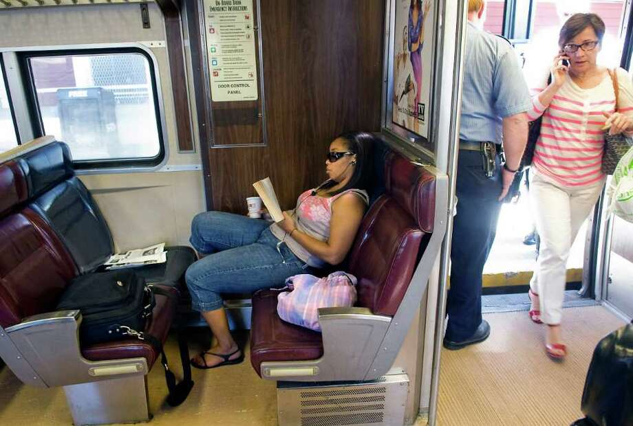Aracelis Warren reads on the Metro-North train as passengers board while talking on cell phones en route to Grand Central Station from Greenwich, Conn. on Friday July 1, 2011. Metro-North is considering the introduction of quiet cars and is running a trial on the West of Hudson service between Pt. Jervis and Hoboken. Photo: Kathleen O'Rourke / Stamford Advocate
