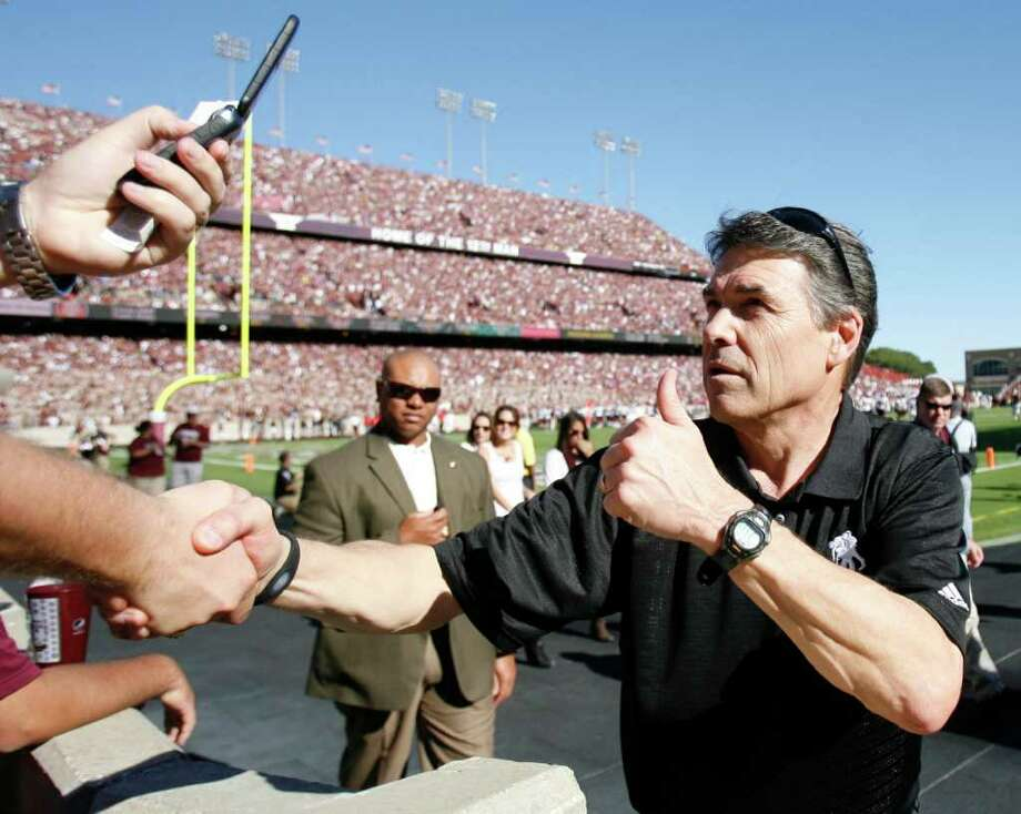 Texas Governor Rick Perry says hello to Texas A&M fans in the first quarter of an NCAA football game between Texas A&M and Texas Tech, Oct. 30, 2010, at Kyle Field in College Station. Photo: Nick De La Torre, Staff / Houston Chronicle