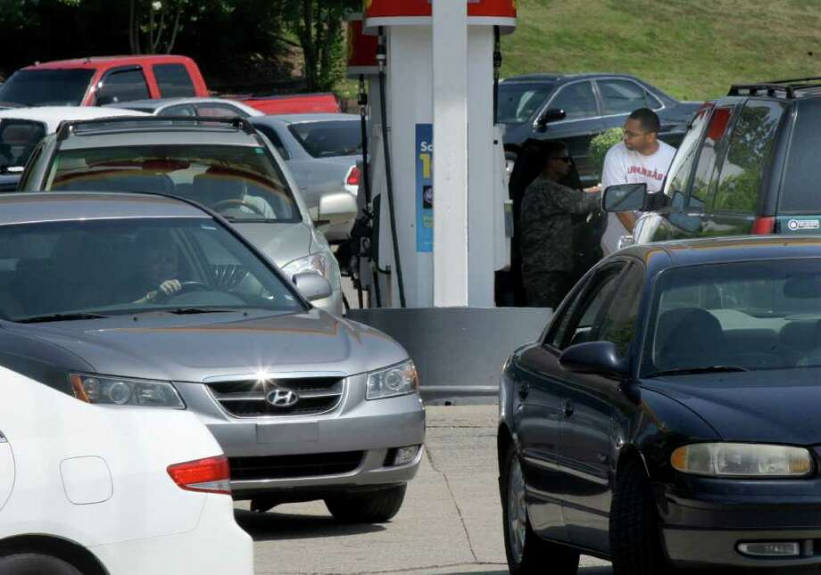 FILE - In this July 1, 2011 file photo, a man pumps gas at a crowded Shell gas station in Little Rock, Ark. Oil is climbing as analysts ratchet up price forecasts for next year as supplies get tighter.(AP Photo/Danny Johnston, file) Photo: Danny Johnston