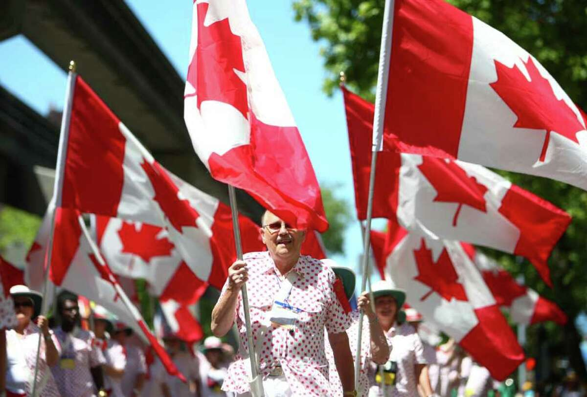 Participants carry Canadian flags during the Lions International Parade on Tuesday, July 5, 2011 along 5th Avenue in Seattle. The nearly 3 1/2 hour parade featured tens of thousands of Lions International members from around the globe. The parade was part of the organization's convention, which is taking place in the Emerald City from July 4th thru 8th. The parade was Seattle's longest ever.