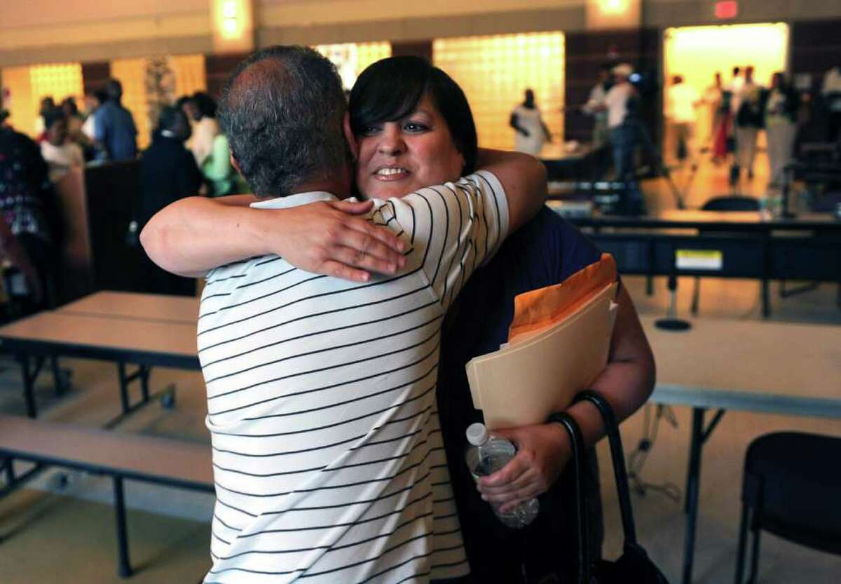Bridgeport Board of Education member Maria Pereira receives a hug by Central high School social worker Steven Karjanis for her statement made at a special meeting held at Cesar A. Batalla Elementary School in Bridgeport, Conn. on Tuesday July 5, 2011.