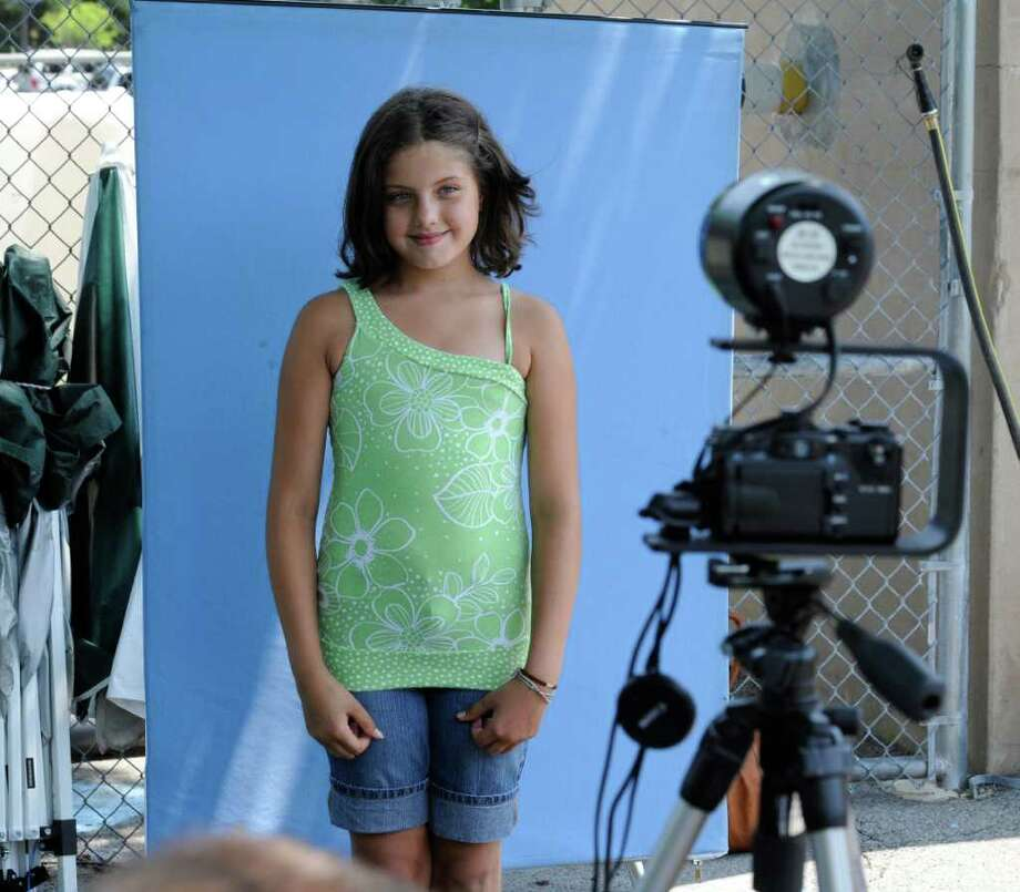 Mikayla Pierce, 10 stands for her ID photo at the Operation Safe Child booth set up at the Central Park Pool in Schenectady, N.Y. by the Schenectady County Sheriff's Office July 5, 2011.   (Skip Dickstein/ Times Union) Photo: Skip Dickstein